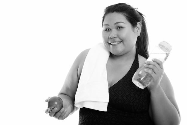 Perto de uma jovem linda mulher asiática com excesso de peso pronta para a academia isolada