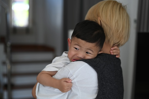 Perto de uma jovem mãe tentando acalmar seu filho bebê chorando em casa