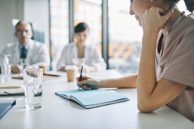Perto de uma jovem médica tomando notas em um seminário médico na sala de conferências, copie o espaço