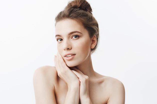 Perto de uma jovem morena atraente com penteado de coque e ombros nus, segurando as mãos perto do rosto, com expressão de rosto calmo e relaxado.