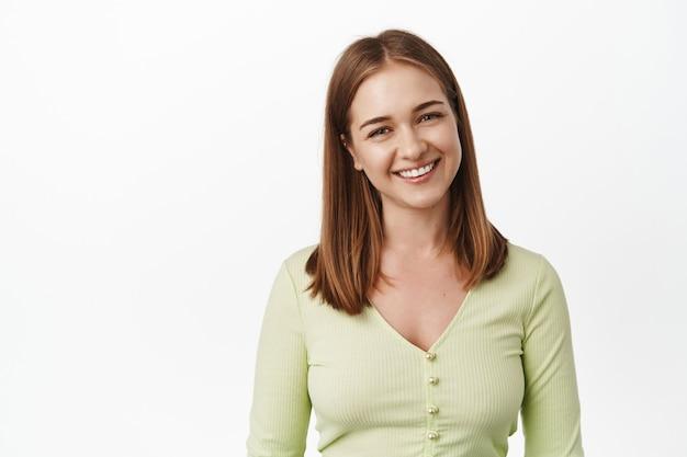 Perto de uma jovem mulher agradável, sorrindo e olhando a expressão amigável, feliz bonito rosto, sorria dentes brancos, em pé na blusa casual contra a parede branca.