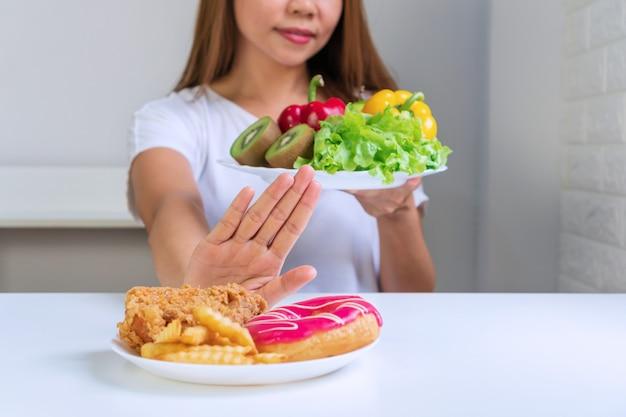 Perto de uma jovem mulher asiática, usando a mão empurrando seu frango frito favorito,