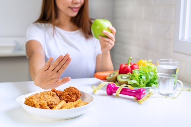 Perto de uma jovem mulher asiática, usando a mão empurrar para fora junk food e escolher comida saudável.