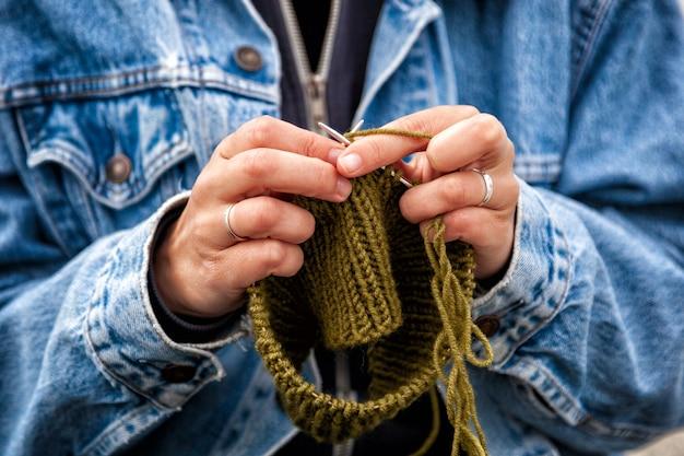 Perto de uma jovem mulher casada, vestida com um casaco de ganga da moda, tricotar um chapéu verde com agulhas de tricô num dia de verão. conceito de vida e trabalho criativo freelance