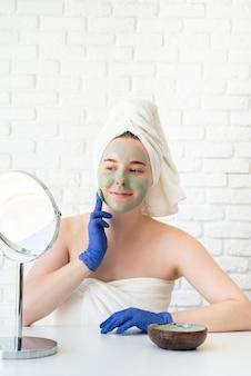 Perto de uma jovem mulher caucasiana feliz em toalhas de banho brancas, usando luvas e aplicando máscara facial de argila, olhando para o espelho