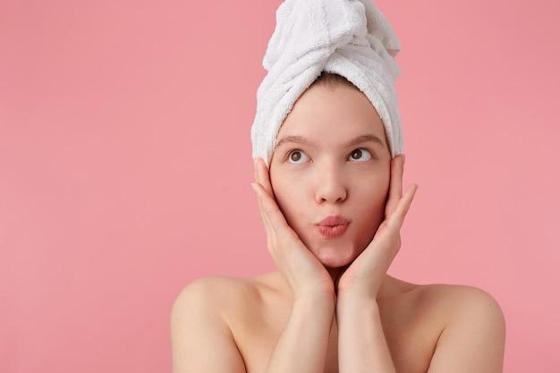 Perto de uma jovem mulher feliz após o banho com uma toalha na cabeça, sonhadoramente olhando para longe com as palmas das mãos nas bochechas, em pé.