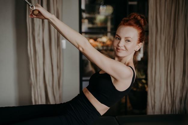 Perto de uma jovem mulher feliz com cabelo vermelho, fazendo exercícios de alongamento do braço no reformador de pilates no estúdio de fitness, sorrindo para a câmera durante o treinamento no estúdio de fitness. conceito de pessoas esportivas
