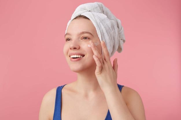 Perto de uma jovem mulher simpática com beleza natural com uma toalha na cabeça depois do banho, sorrindo, olhando para longe e coloca creme facial.