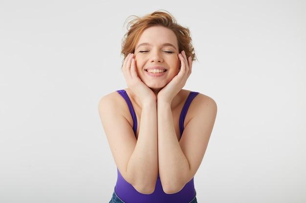 Perto de uma jovem simpática senhora de cabelos curtos usa uma camisa roxa e jeans, fecha os olhos e sonha com um vestido novo, toca suas bochechas e.