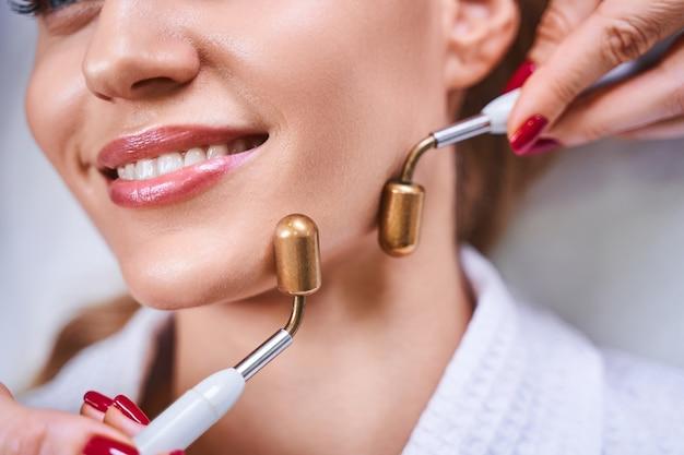 Perto de uma jovem sorridente visitando um cosmetologista por usar tratamento de microcorrentes em seu rosto