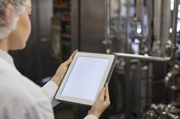 Perto de uma jovem trabalhadora segurando um tablet digital com uma tela em branco contra equipamentos de fábrica no fundo, copie o espaço