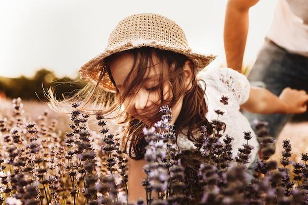 Perto de uma linda criança brincando em um campo de flores. menina feliz rindo enquanto coleta flores em um campo contra o pôr do sol.