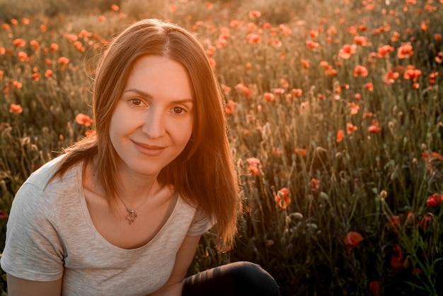 Perto de uma linda garota com cabelo comprido, posando em um campo com papoulas ao pôr do sol