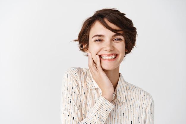 Perto de uma linda garota com cabelo curto, sorrindo com dentes brancos e tocando o rosto limpo e natural, em pé sobre a parede