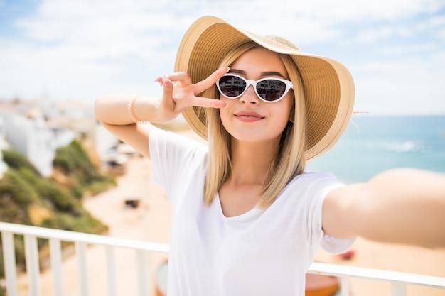 Perto de uma linda jovem com chapéu de verão tirando uma selfie e mostrando um gesto de paz na praia