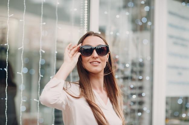 Perto de uma linda jovem sorridente sorrindo, escolhendo e escolhendo os óculos na esquina da ótica no shopping