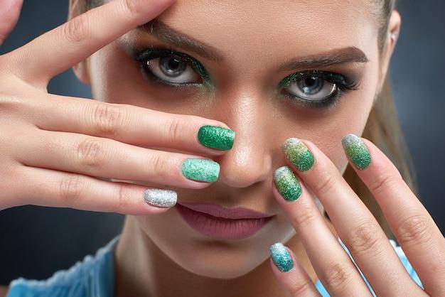 Perto de uma linda mulher morena com manicure brilhante, maquiagem em cores verdes, pele bronze. garota atraente posando, escondendo o rosto, mostrando as unhas. conceito de beleza.