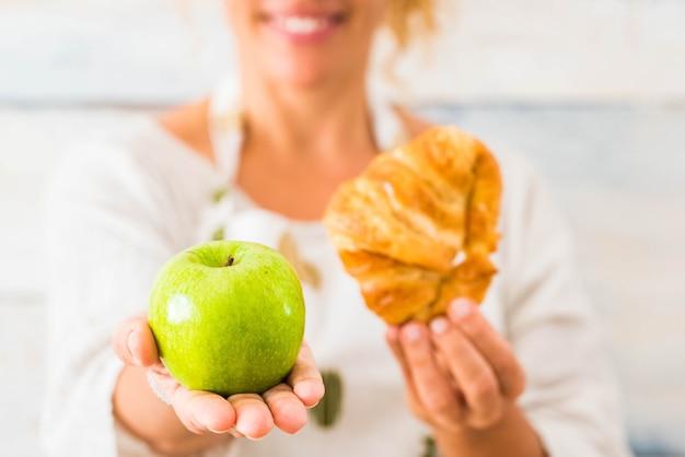 Perto de uma linda mulher segurando uma maçã e um croissant na frente da câmera, escolhendo entre uma vida saudável ou um estilo de vida pouco saudável - fazer dieta e cuidar da comida