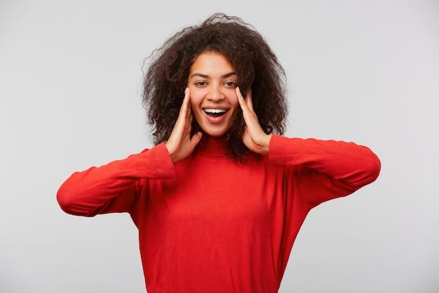 Perto de uma linda mulher surpresa com um penteado afro com a boca bem aberta olhando para a frente