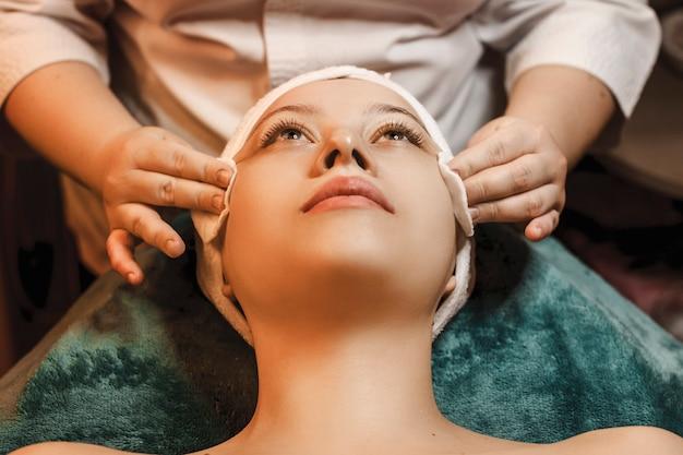 Perto de uma linda mulher tendo procedimentos de cuidados da pele em um centro de spa de bem-estar.
