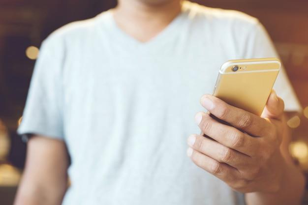 Perto de uma mão de homem segurando usando celular ao ar livre do telefone móvel inteligente em parque público.