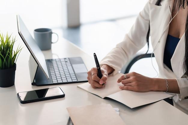 Perto de uma mão de mulher de negócios tomando notas em um papel em branco com um tablet e smartphone colocado no escritório.
