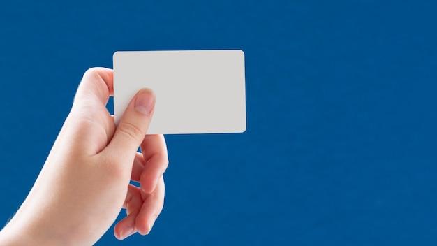 Perto de uma mão feminina segurando um cartão de visita branco em branco sobre um fundo azul. ideia de negócio, copie o espaço.