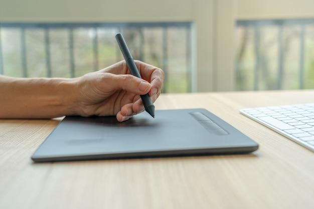 Perto de uma mão usando a mesa digitalizadora para vídeo-arte.