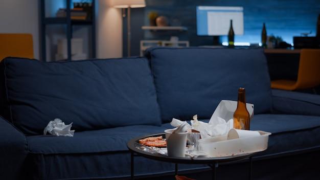 Perto de uma mesa bagunçada com sobras na sala de estar vazia e desorganizada
