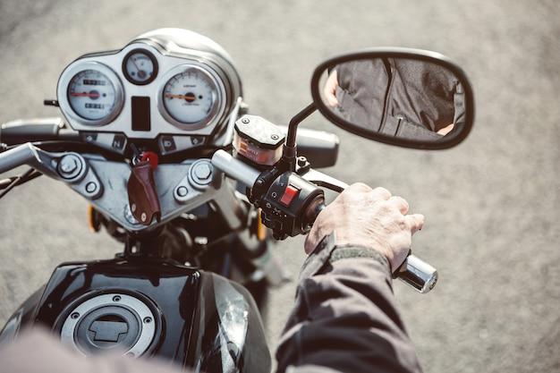 Perto de uma motocicleta de direção de mão de homem sênior na estrada