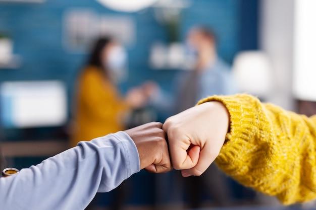 Perto de uma mulher africana e um amigo fazendo colisão de punho cumprimentando um ao outro na sala de estar hme, mantendo o distanciamento social como precaução de segurança durante a pandemia global com coronavírus.