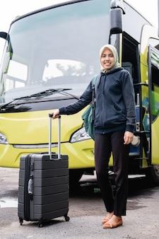 Perto de uma mulher asiática com um véu sorrindo, olhando para a câmera enquanto segura uma mala de costas no fundo do ônibus