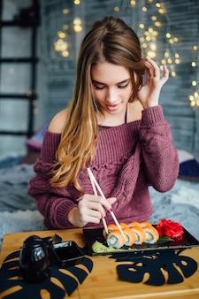Perto de uma mulher atraente e radiante, vestindo um suéter vermelho, tomando café da manhã em casa