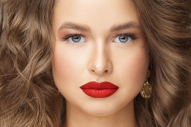 Perto de uma mulher bonita com lindos olhos azuis, cílios grandes e sobrancelhas. conceito de beleza e cuidados