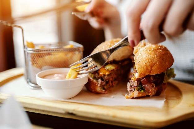Perto de uma mulher caucasiana, comendo um delicioso hambúrguer enquanto está sentado no restaurante.