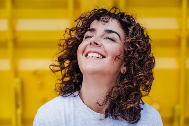 Perto de uma mulher caucasiana feliz com cabelo encaracolado e olhos fechados sobre fundo amarelo. horário de verão. estilo de vida ao ar livre