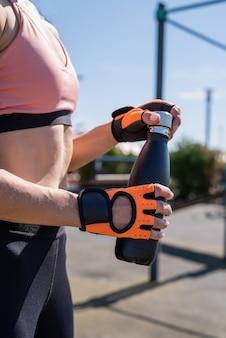 Perto de uma mulher com as mãos em luvas esportivas segurando uma garrafa de água no campo de esportes