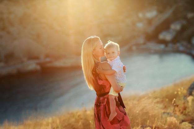 Perto de uma mulher com longos cabelos loiros ao ar livre com um bebê nos braços