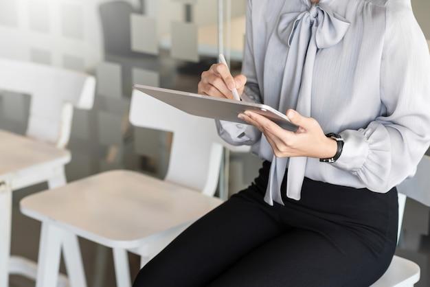 Perto de uma mulher com um tablet, sentada no escritório para uma entrevista de emprego.