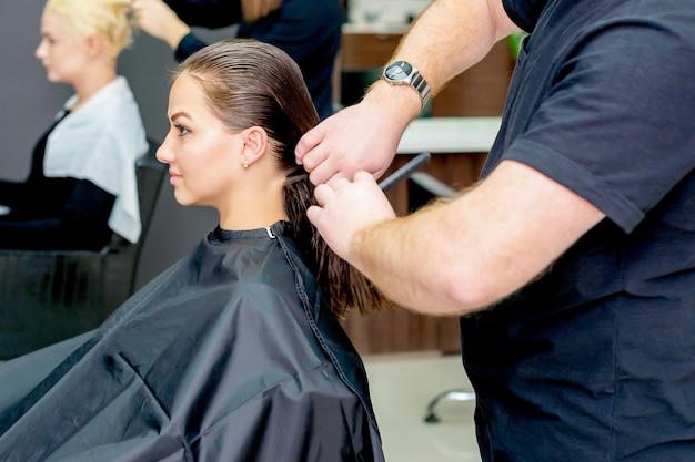 Perto de uma mulher cortando o cabelo de cabeleireiro em um salão de cabeleireiro.