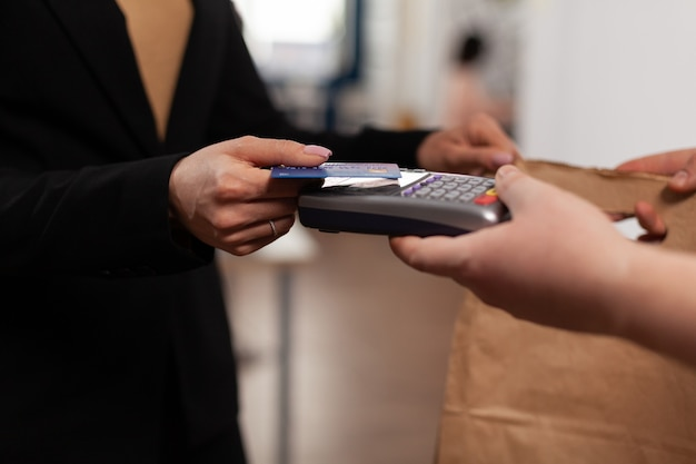 Perto de uma mulher de negócios segurando um cartão de crédito da pos