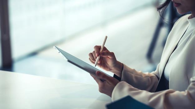 Perto de uma mulher de negócios segurando uma caneta, trabalhando em um tablet no escritório.