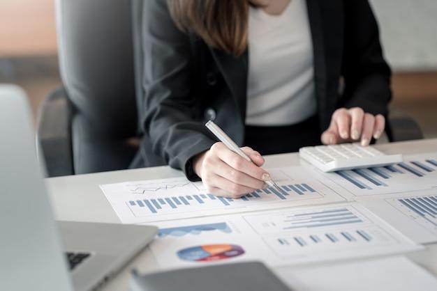 Perto de uma mulher de negócios trabalhando em contabilidade, usando gráficos e calculadoras no escritório.