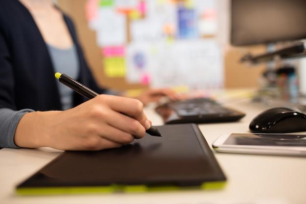 Perto de uma mulher de negócios trabalhando em uma mesa digitalizadora