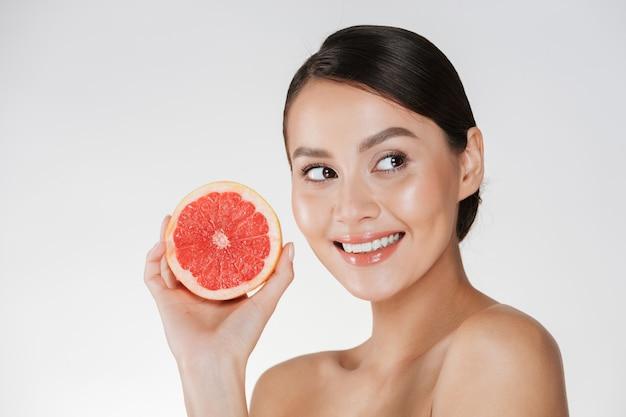 Perto de uma mulher feliz com a pele fresca saudável, segurando a toranja suculenta e olhando de lado com o sorriso, isolado sobre o branco