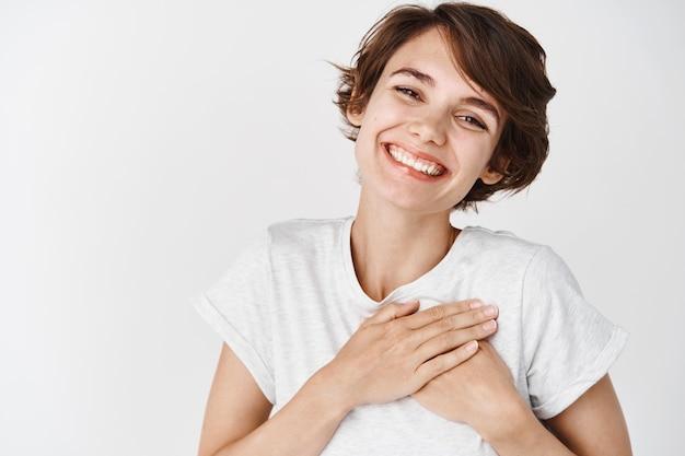 Perto de uma mulher feliz e sorridente, dizer obrigado, segurando um coração agradecido, expressar gratidão, encostado na parede branca