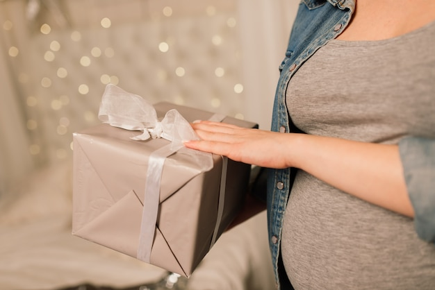 Perto de uma mulher grávida sorridente e feliz tocando sua barriga sobre o fundo da árvore de natal