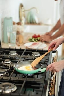 Perto de uma mulher irreconhecível cozinhando o café da manhã na cozinha de casa com foco em ovos fritos na frigideira, copie o espaço