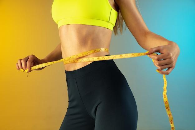 Perto de uma mulher jovem e esportiva com barriga em forma e medidor em corpo perfeito de fundo gradiente