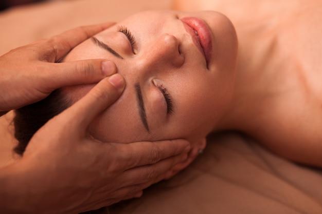 Perto de uma mulher linda feliz sorrindo com os olhos fechados, recebendo massagem relaxante na cabeça. jovem mulher atraente, desfrutando de massagem de rosto no centro de bem-estar. cuidados com a pele, saúde, mimos